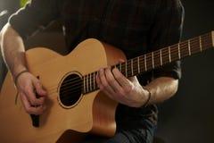 Feche acima do homem que joga a guitarra acústica no estúdio Imagem de Stock