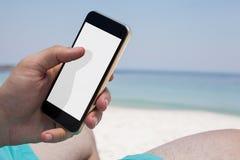 Feche acima do homem que usa o smartphone na praia fotos de stock royalty free