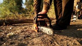 Feche acima do homem que usa a serra de cadeia para cortar a madeira filme