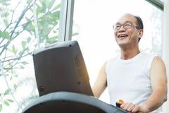 Feche acima do homem superior asiático que exercita na máquina da escada rolante com c Fotos de Stock