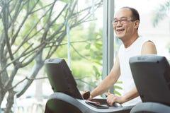 Feche acima do homem superior asiático que exercita na máquina da escada rolante com c Fotografia de Stock Royalty Free