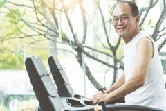 Feche acima do homem superior asiático que exercita na máquina da escada rolante com c Fotos de Stock Royalty Free