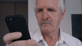 Feche acima do homem superior com bigode usando o telefone esperto em casa na cozinha filme