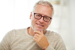 Feche acima do homem superior de sorriso no pensamento dos vidros imagem de stock royalty free