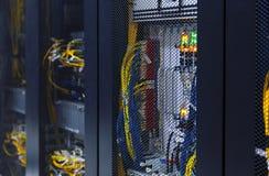 Feche acima do interior moderno da sala do servidor com computador super, fios e cabos sob a porta engrenada Centro de dados com  fotografia de stock royalty free