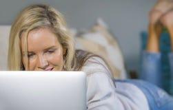Feche acima do Internet de utilização relaxado louro bonito e feliz do retrato da mulher 40s em casa no encontro de trabalho do p Imagem de Stock