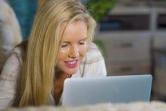 Feche acima do Internet de utilização relaxado louro bonito e feliz do retrato da mulher 40s em casa no encontro de trabalho do p Imagem de Stock Royalty Free