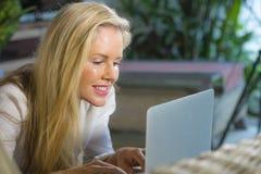 Feche acima do Internet de utilização relaxado louro bonito e feliz do retrato da mulher 40s em casa no encontro de trabalho do p Imagens de Stock