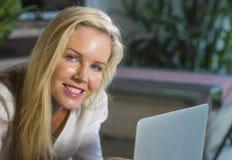 Feche acima do Internet de utilização relaxado louro bonito e feliz do retrato da mulher 40s em casa no encontro de trabalho do p Fotografia de Stock