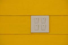 Feche acima do interruptor branco da eletricidade ou do fundo claro da parede da cor do amarelo do switchon imagens de stock