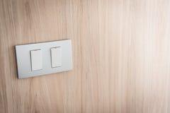 Feche acima do interruptor da luz cinzento no fundo de madeira imagens de stock