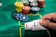 Feche acima do jogador de pôquer com os dois cartões e microplaquetas de jogo dos áss na tabela verde do casino Fotos de Stock