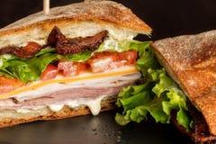 Feche acima do lado do corte de um sanduíche de clube que vaza com molhos Imagens de Stock Royalty Free