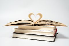 Feche acima do livro aberto com o coração dado forma de duas páginas, isoladas no fundo branco foto de stock royalty free