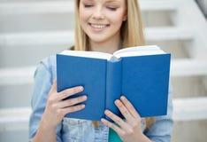 Feche acima do livro de leitura da jovem mulher na escola Imagem de Stock