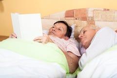 Livro de leitura superior dos pares na cama Imagens de Stock