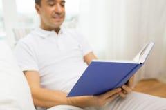 Feche acima do livro de leitura feliz do homem em casa Foto de Stock Royalty Free