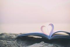 Feche acima do livro do coração na areia na praia com fundo do borrão do filtro do vintage imagem de stock royalty free