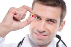 Feche acima do médico que guarda o comprimido amarelo-vermelho pequeno Fotos de Stock Royalty Free