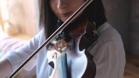 Feche acima do músico da mulher na camisa branca que joga o violino video estoque