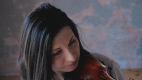 Feche acima do músico da mulher na camisa branca que joga o violino filme