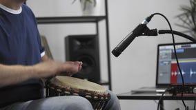 Feche acima do músico que joga o djembe para rufar o instrumento no estúdio da música da casa filme