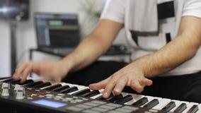 Feche acima do músico que joga o teclado de midi no estúdio da música da casa video estoque