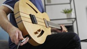 Feche acima do músico que obstrui na guitarra elétrica no estúdio da música da casa video estoque