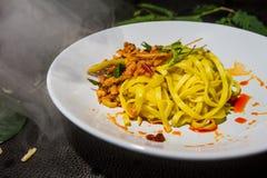 Feche acima do macarronete amarelo fritado de Tom yum, placas brancas arranjadas em um fundo preto Alimento tailandês tradicional imagens de stock royalty free
