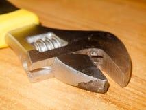 Feche acima do macro da ferramenta mecânica da chave inglesa do metal na tabela foto de stock