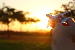 feche acima do man& x27; mão de s que mantém o avião do brinquedo contra o céu do por do sol Fotografia de Stock