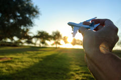 feche acima do man& x27; mão de s que mantém o avião do brinquedo contra o céu do por do sol Imagem de Stock Royalty Free