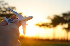 feche acima do man& x27; mão de s que mantém o avião do brinquedo contra o céu do por do sol Foto de Stock Royalty Free