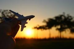 feche acima do man& x27; mão de s que mantém o avião do brinquedo contra o céu do por do sol Imagens de Stock Royalty Free