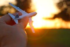 feche acima do man& x27; mão de s que mantém o avião do brinquedo contra o céu do por do sol Imagem de Stock