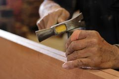 Feche acima do martelo e do prego usando-se pelo carpinteiro na placa de madeira Foco seletivo e profundidade de campo rasa Imagens de Stock Royalty Free