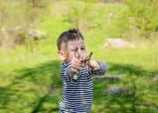 Feche acima do menino que guarda o tiro de estilingue para trás tirado Imagens de Stock Royalty Free