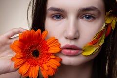 Feche acima do modelo com o olhar natural que guarda a flor alaranjada agrad?vel fotografia de stock