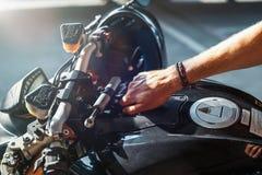 Feche acima do motociclista que liga o motor da motocicleta no estacionamento foto de stock