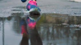 Feche acima do movimento lento disparado dos pés de um corredor nas sapatilhas Os esportes fêmeas equipam movimentar-se fora em u