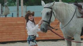 Feche acima do nariz de acariciamento do ` s do cavalo da moça lentamente vídeos de arquivo