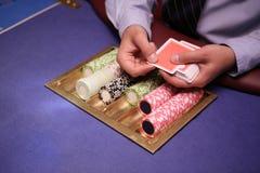 Feche acima do negociante do holdem com cartões e microplaquetas de jogo na tabela azul Foto de Stock