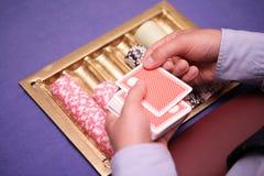 Feche acima do negociante do holdem com cartões e microplaquetas de jogo na tabela azul Fotografia de Stock Royalty Free