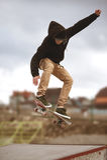 Feche acima do os pés dos skateres quando desempenho ativo de patinagem do adolescente do conluio disparado no ar em um skate na Imagem de Stock