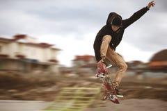Feche acima do os pés dos skateres quando desempenho ativo de patinagem do adolescente do conluio disparado no ar em um skate na Foto de Stock