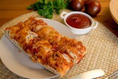 Feche acima do pão do focaccia em uma mesa de cozinha com tomates, molho de tomate, e salsa fotografia de stock