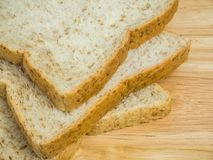 Feche acima do pão integral inteiro de três fatias na tabela de madeira Fotos de Stock