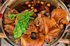 Feche acima do pé cozido da carne de porco com o ovo no potenciômetro de aço inoxidável Imagem de Stock Royalty Free