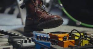 Feche acima do pé do guitarrista que pressiona o pedal filme