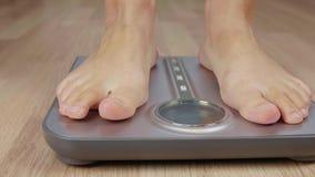 Feche acima do pé do homem ou da mulher que pisa na escala do peso para tornar mais pesado o corpo video estoque